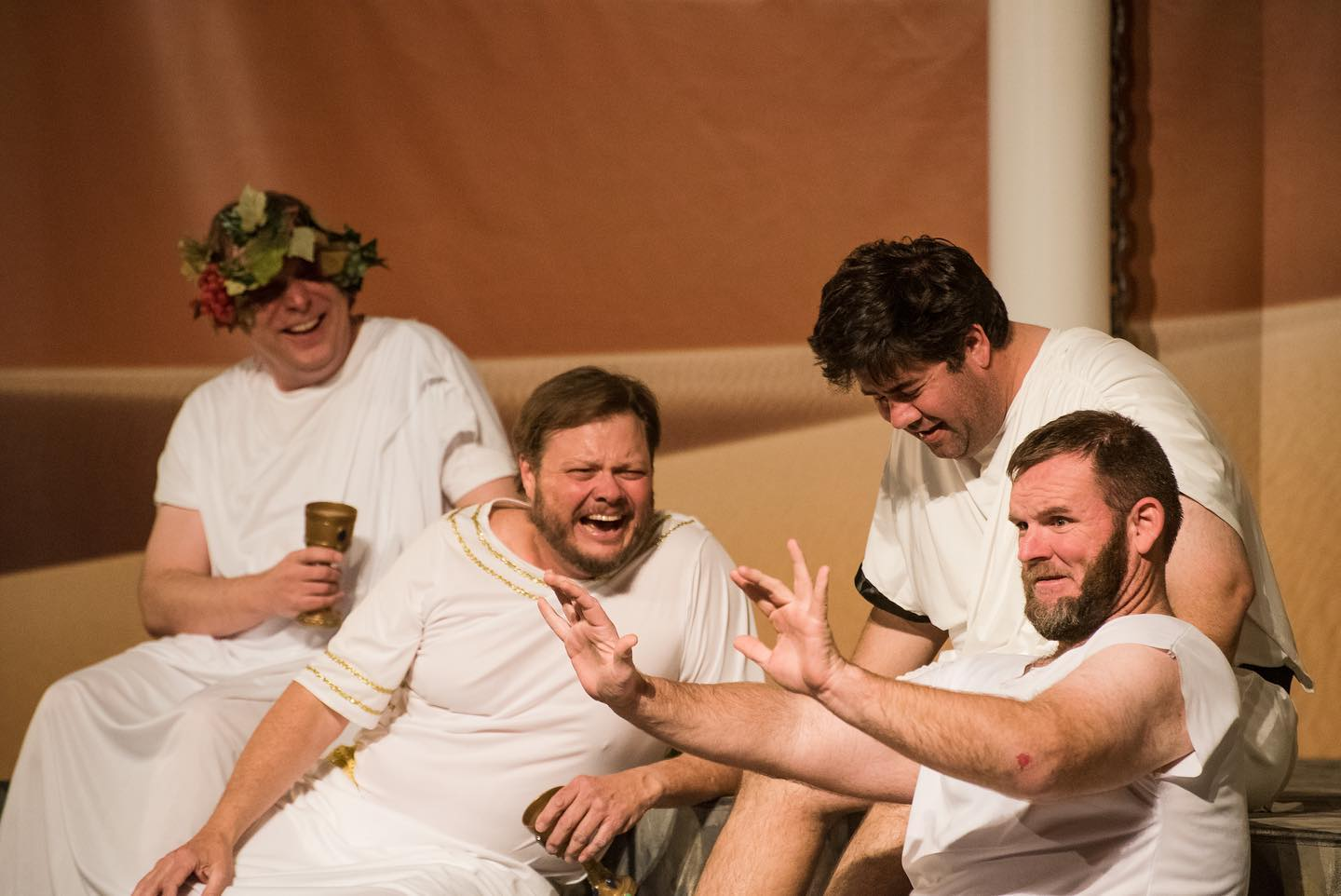Men in white garments are seen laughing and chatting close together