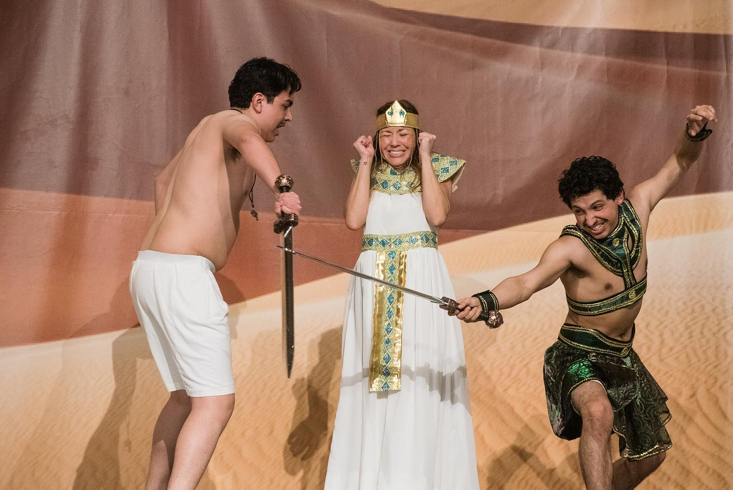 An egyptian monarch is showing frustration as a person (presumably a slave) is lashing out at another man in front. These are all actors.