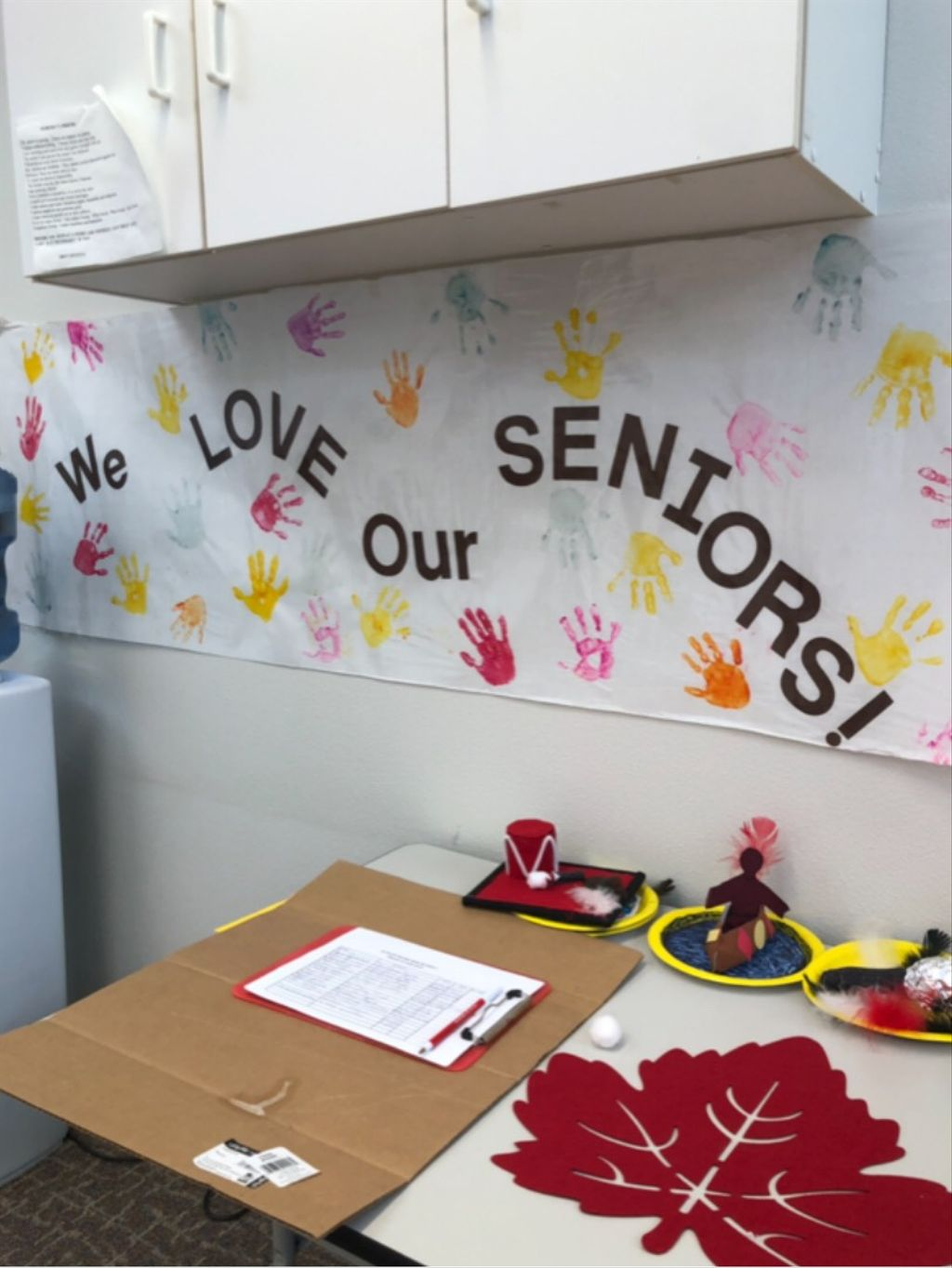 "Decorated office space with painted handprints and text that reads ""We love our seniors!"""