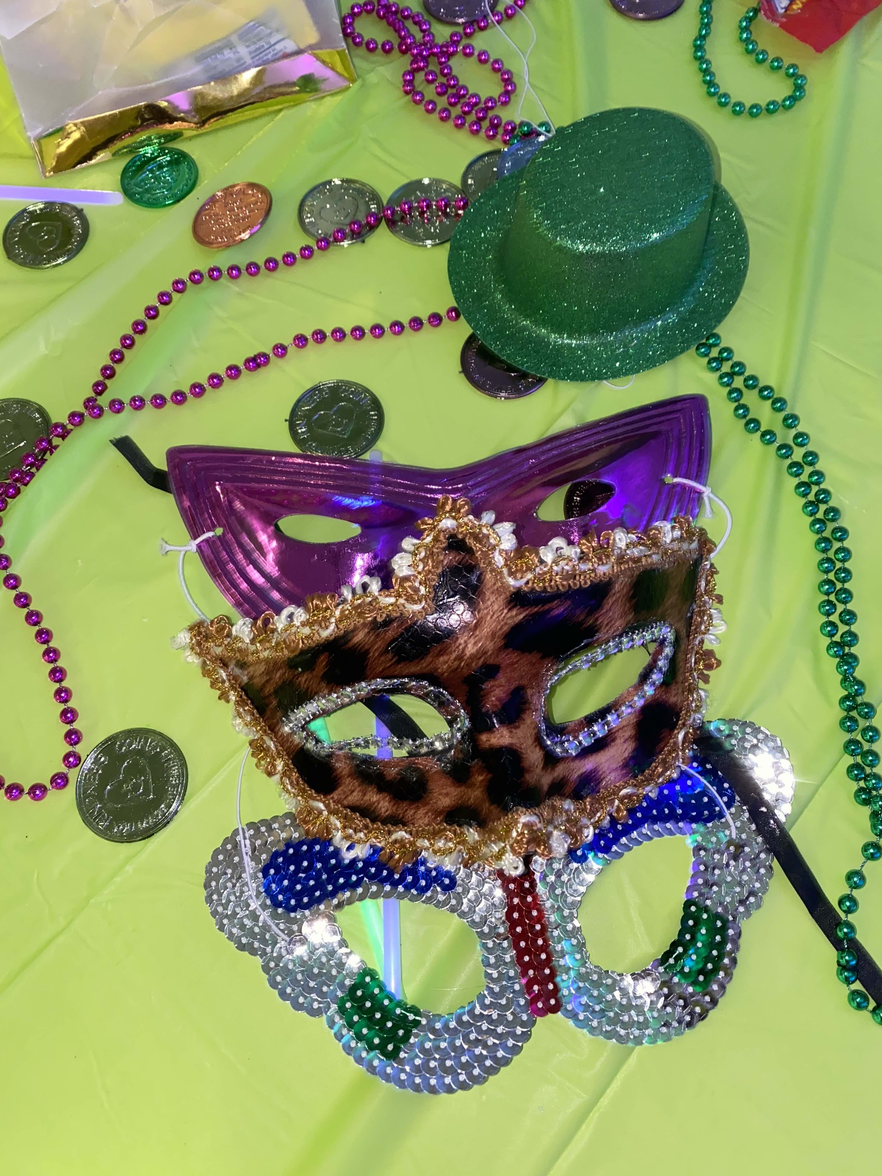 mardi gras masks, beads, coins, and a hat are strewn on a green table