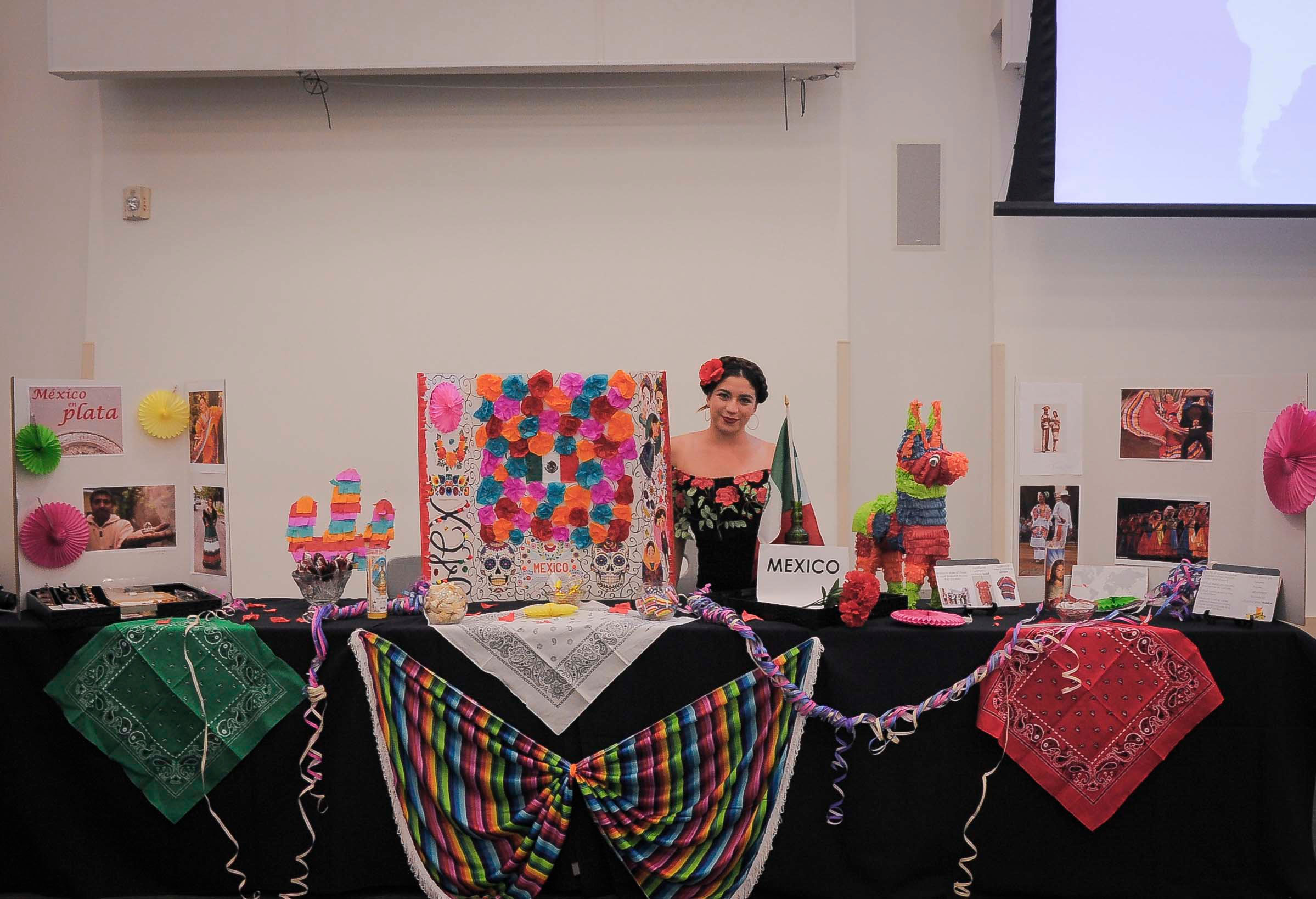 "Girl stands behind bright and colorful ""Mexico"" table. Flowers, a piñata, and paper decor surround her."