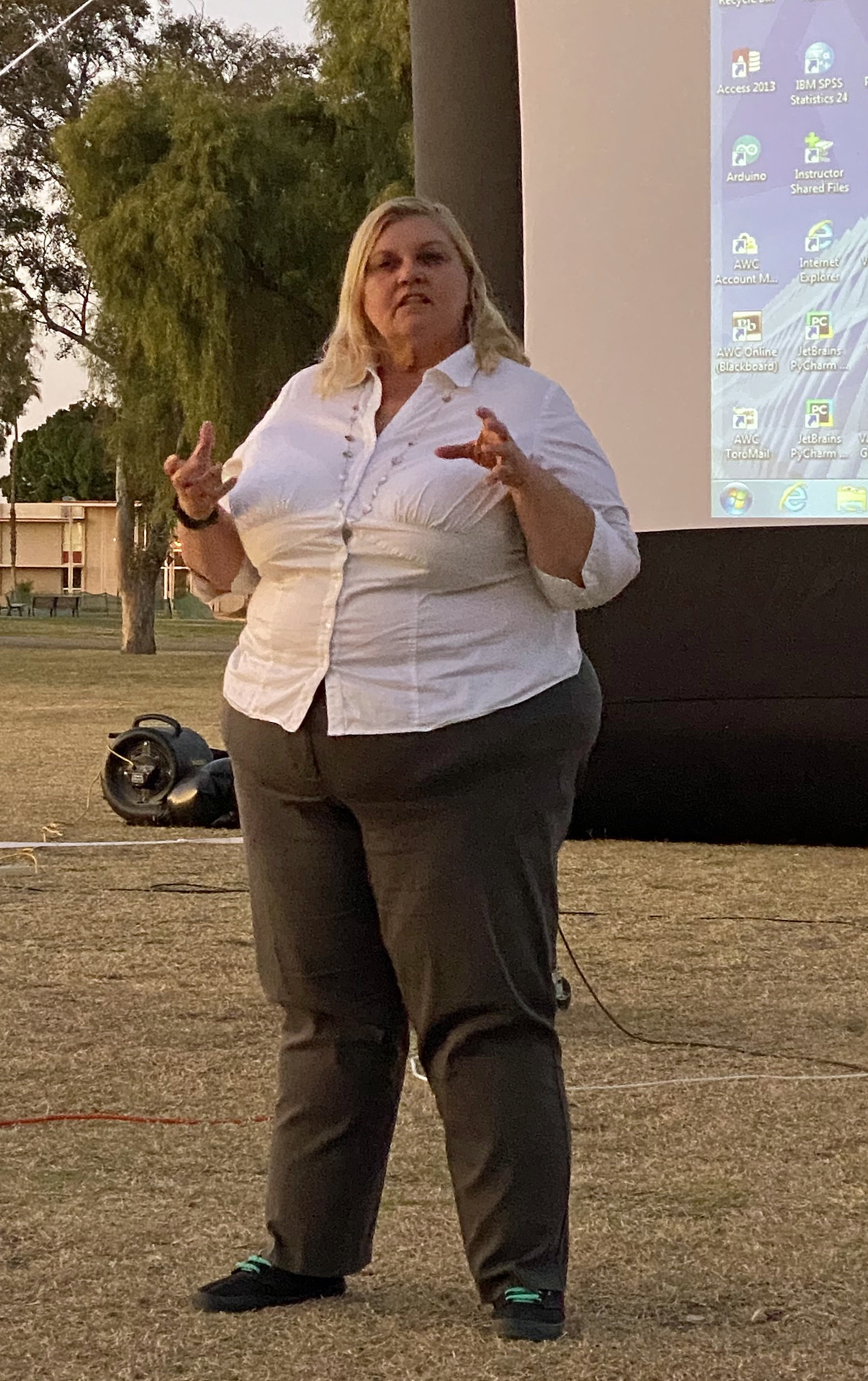 A blonde woman in a white shirt is speaking outdoors in front of a projection screen.