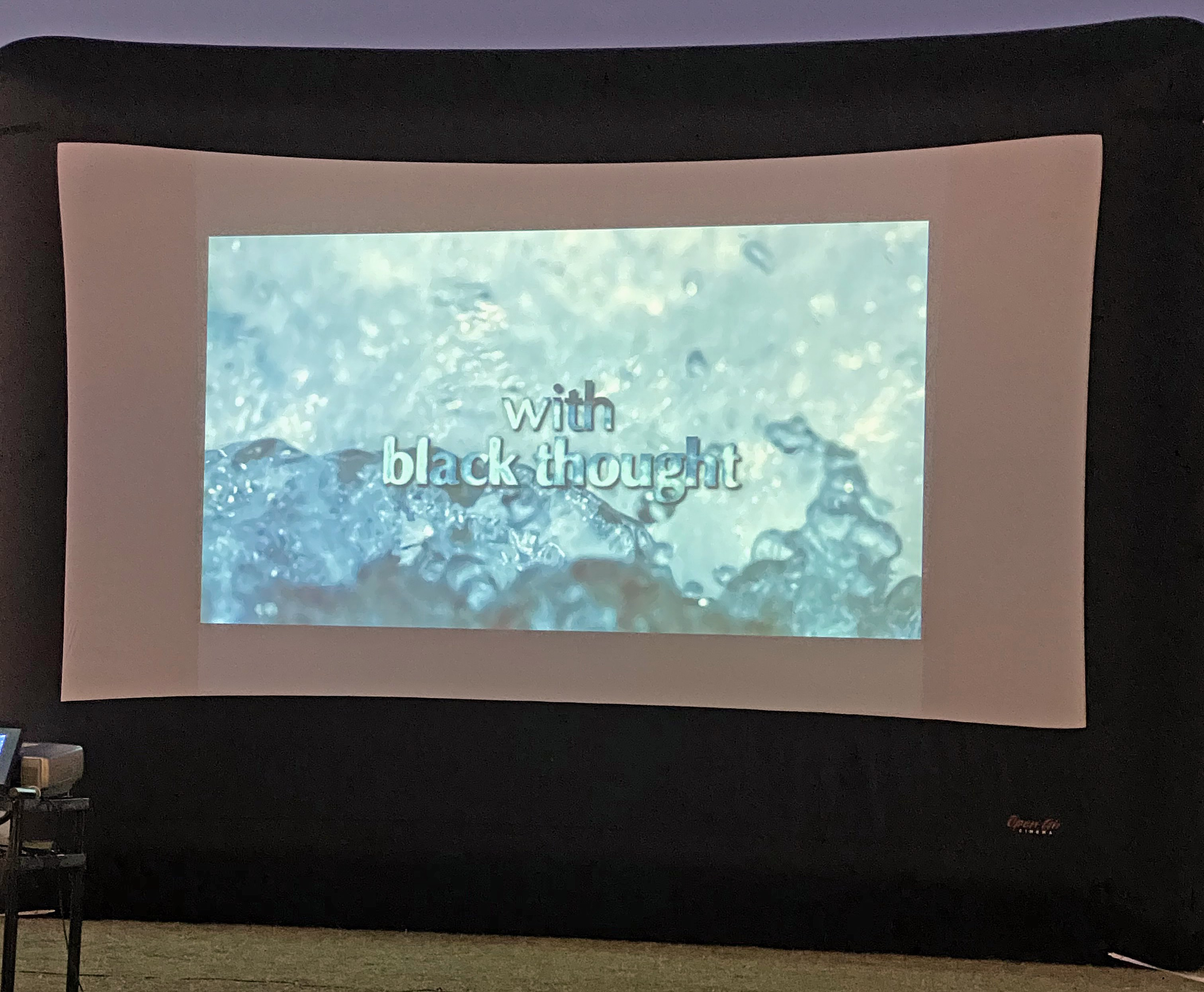 "a projection screen shows a watery background with the words ""With black thought"""