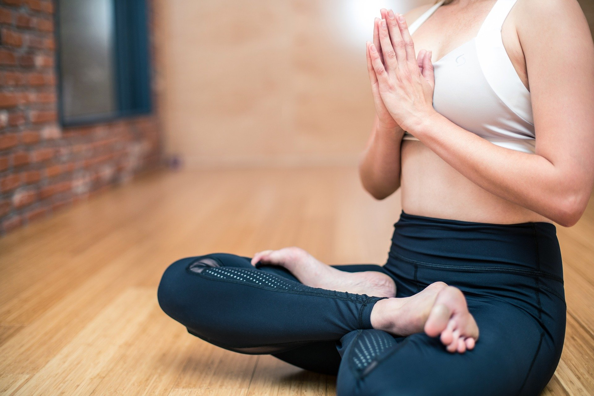 a body poised in a yoga, cross-legged position on wood flooring. head is out of frame.