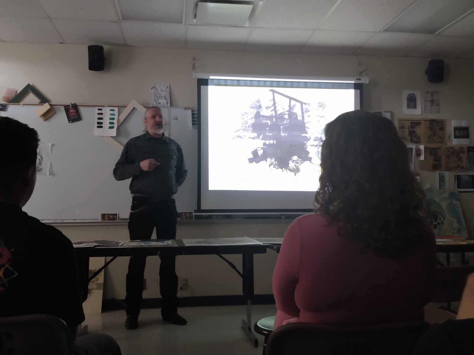 A man is presenting in front of a projector