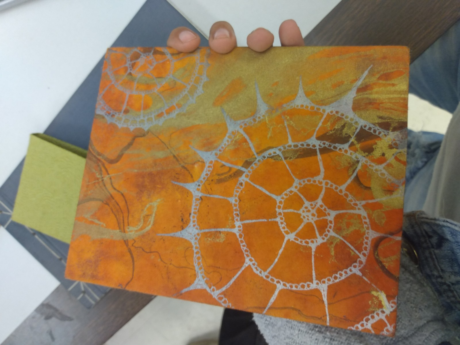 Orange-colored art with a shell pattern is pictured