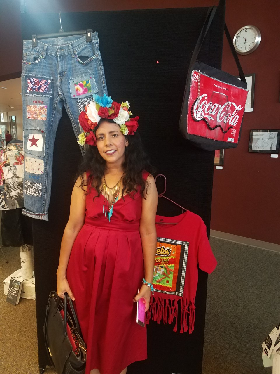 A woman in a red dress and flower crown standing beside mixed media art/clothing
