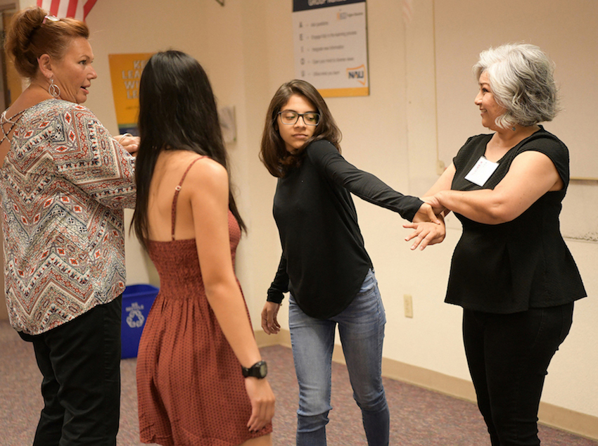 Instructor teaching group of women a self-defense tactic.