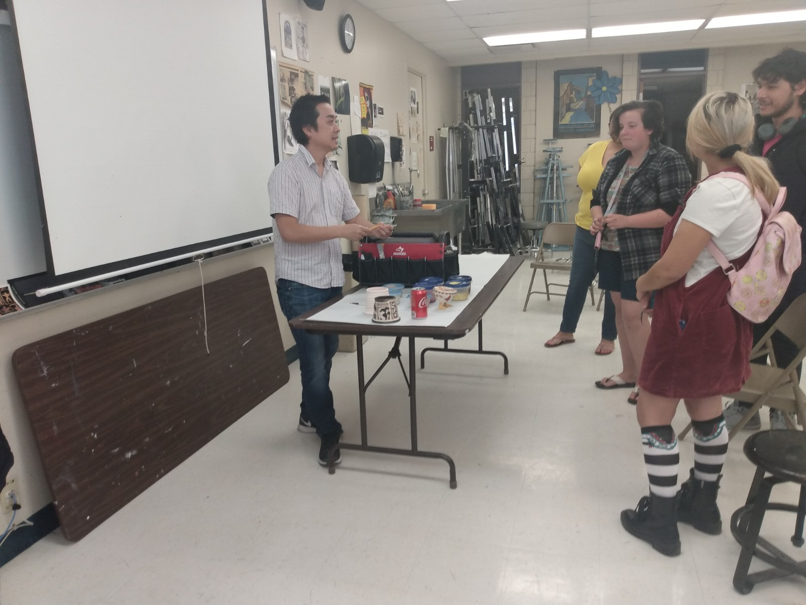 people are standing as a man at a table presents his art