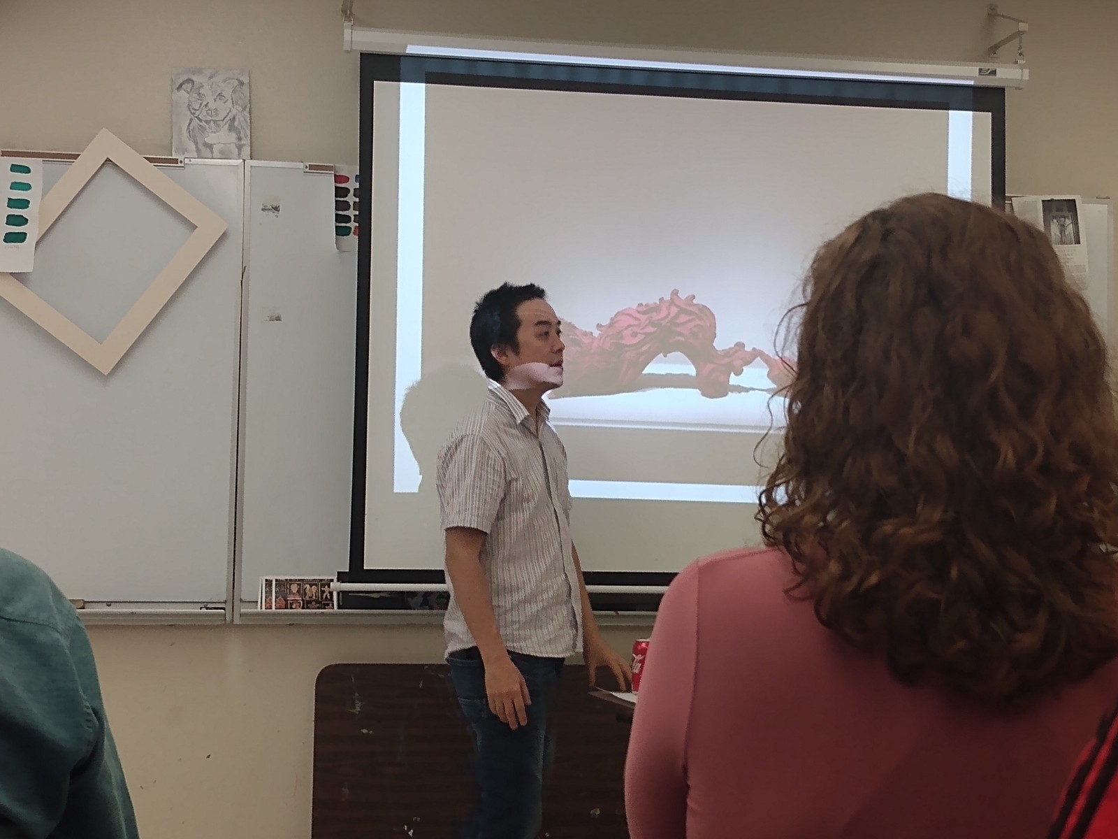 A person is presenting in front of a screen to an audience