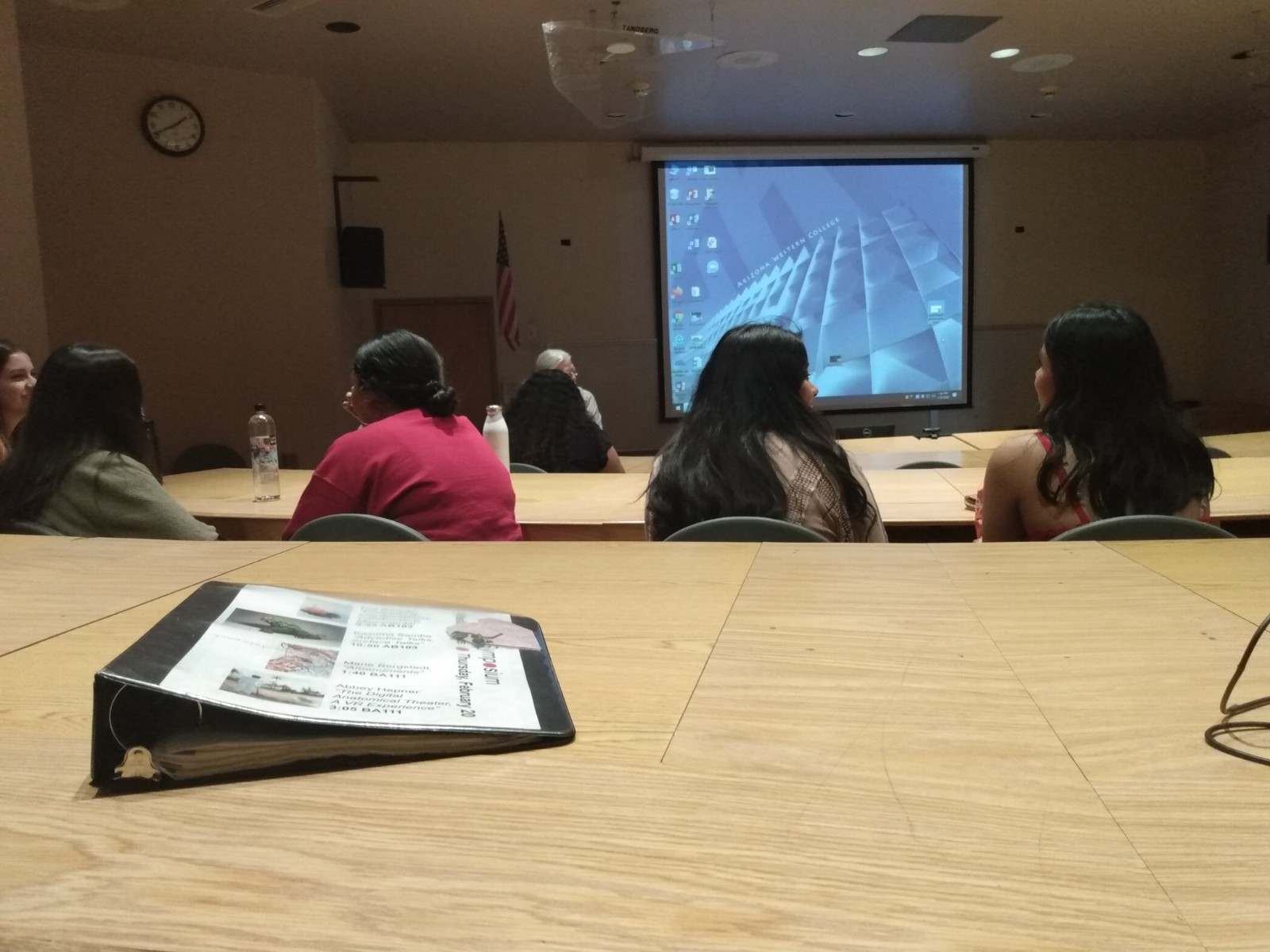 A seat at a table--multiple rows of people in front of a projector