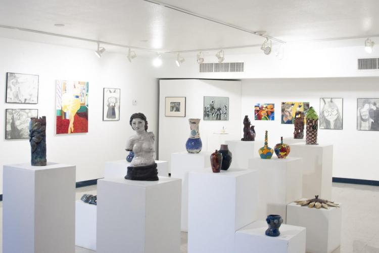 A lot of art pieces (paintings and sculptures) in a large white space