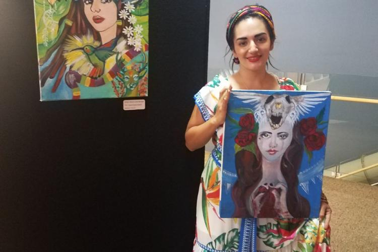 A woman dressed like Frida Kahlo holding up a painting by another painting.