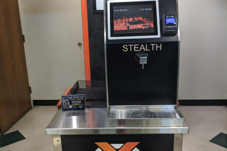 """Water dispenser with orange and black colors and the text """"Stealth"""""""