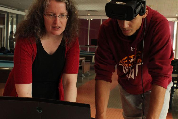 Two people looking at a computer as if they were setting it up