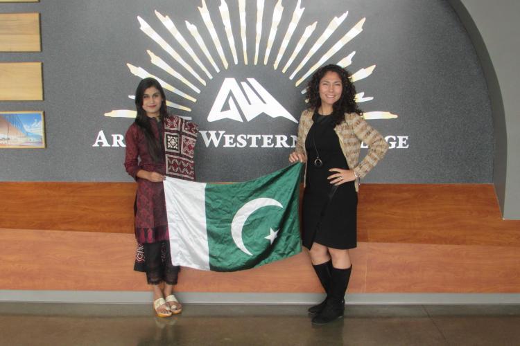 Two women hold up a Pakistani flag. one is wearing traditional Pakistani dress.