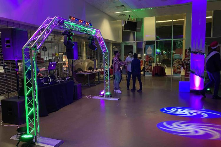 people stand in a colorfully lit (purple and green) cafeteria party.