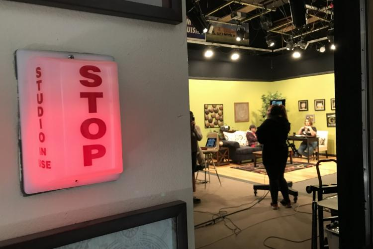 A red STOP light is on, indicating the studio in front is recording