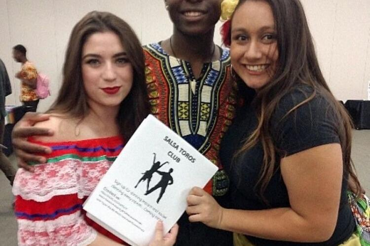 two women and a man pose with a salsa dance booklet