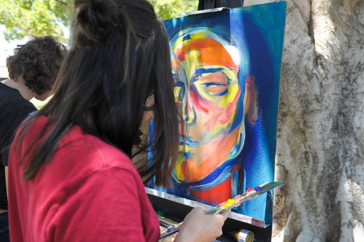 A person in red is standing outside painting on a canvas which is already blue with an orange face