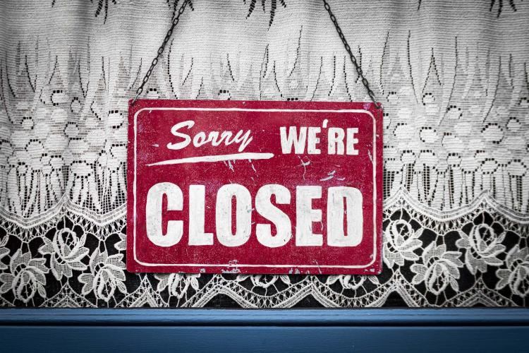 "A red ""sorry, we're closed sign"" is hung in front of a lacy curtain"
