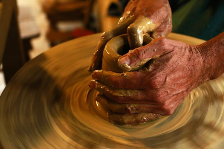 hands are molding a piece of clay on a spinning pottery board.