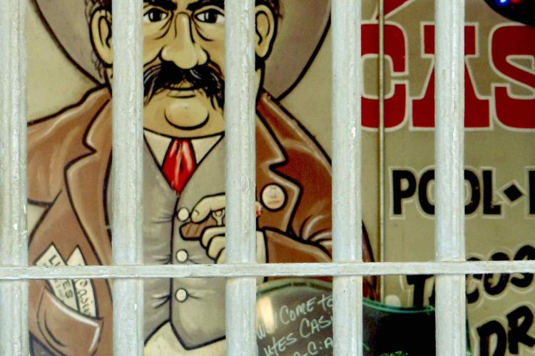 A classic art of a man with a big black mustache and cowboy hat is shown behind bars. The art is typically associated with Lutes Casino